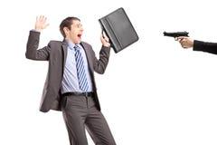 Uomo d'affari spaventato da una mano che tiene una pistola Fotografia Stock