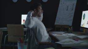 Uomo d'affari stanco che allunga e che sbadiglia vicino al computer nell'ufficio di notte video d archivio