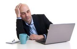 Uomo d'affari stanco che dorme su un computer portatile Fotografia Stock