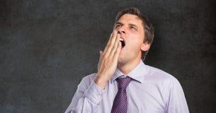 Uomo d'affari stanco che sbadiglia contro la lavagna Fotografie Stock
