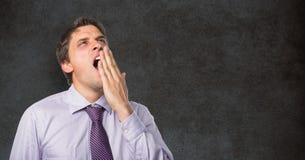 Uomo d'affari stanco che sbadiglia contro la lavagna Fotografie Stock Libere da Diritti