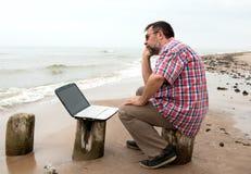 Uomo d'affari stanco che si siede con il taccuino sulla spiaggia Fotografia Stock