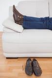Uomo d'affari stanco che si trova sul sofà con le scarpe fuori Immagini Stock