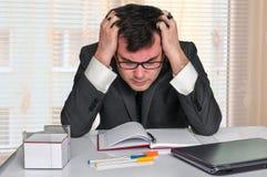 Uomo d'affari stanco con il computer portatile nell'ufficio Fotografia Stock