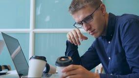 Uomo d'affari stanco dei giovani o ubriaco sovraccarico Typing sulla tastiera del computer portatile, sul caffè bevente e sulla c stock footage