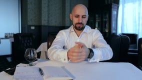 Uomo d'affari stanco e frustrato che si siede in un caffè video d archivio