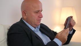 Uomo d'affari stanco e turbato Rest che si siede sul sofà e sul testo facendo uso del cellulare archivi video