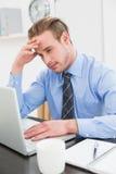 Uomo d'affari stanco facendo uso del suo computer portatile Immagini Stock Libere da Diritti