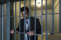 Uomo d'affari Standing Behind Bars Fotografia Stock Libera da Diritti