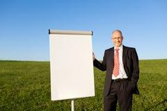 Uomo d'affari Standing By Blank Flipchart sul campo erboso Fotografie Stock Libere da Diritti