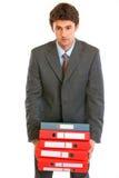 Uomo d'affari stressante che tiene i dispositivi di piegatura pesanti Fotografie Stock Libere da Diritti
