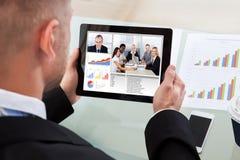 Uomo d'affari su un video o su una teleconferenza sulla sua compressa Fotografia Stock Libera da Diritti
