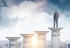 Uomo d'affari su una colonna in una città immagini stock