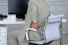 Uomo d'affari Suffering From Backache mentre sedendosi sulla sedia Immagine Stock