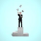 Uomo d'affari sui simboli di lancio e di cattura del podio dei soldi Fotografia Stock