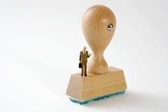 Uomo d'affari sui timbri di gomma di legno, isolati Immagine Stock