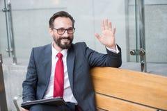 Uomo d'affari sul banco con i colleghi di benvenuto della compressa dall'ufficio La gente di affari professionale fa la riunione  fotografie stock libere da diritti