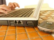 Uomo d'affari sul cellulare e sul documento del computer portatile Fotografia Stock