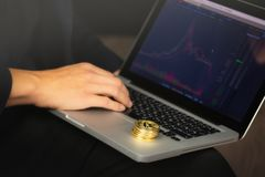 Uomo d'affari sul computer portatile con le monete del bitcoin immagini stock