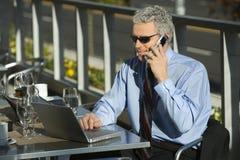 Uomo d'affari sul computer portatile e sul cellulare. Fotografia Stock Libera da Diritti