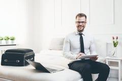 Uomo d'affari sul letto che lavora con una compressa e un computer portatile dalla sua camera di albergo Immagini Stock