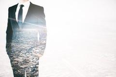 Uomo d'affari sul multiexposure del fondo della città immagine stock
