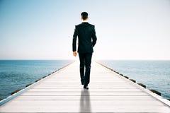 Uomo d'affari sul pilastro del mare Fotografia Stock