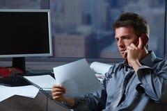 Uomo d'affari sul telefono che controlla documento Fotografia Stock