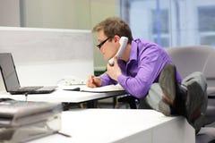 uomo d'affari sul telefono che esamina schermo - cattiva posizione di seduta Fotografia Stock