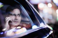 Uomo d'affari sul telefono e sull'osservare fuori la finestra di automobile la notte, luci riflesse Fotografia Stock