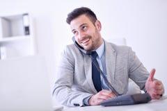 Uomo d'affari sul telefono mentre utilizzando computer portatile nell'ufficio fotografia stock libera da diritti