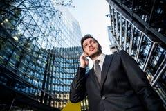 Uomo d'affari sull'edificio per uffici del telefono Immagine Stock