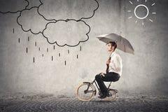 Uomo d'affari sulla bici che tiene un ombrello immagine stock libera da diritti