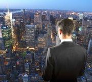 Uomo d'affari sulla cima del grattacielo che esamina i megapolis di notte Immagini Stock