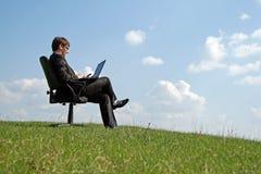 Uomo d'affari sulla presidenza dell'ufficio che funziona con un computer portatile Fotografie Stock Libere da Diritti