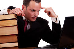 Uomo d'affari sullo scrittorio con i libri, esaminanti calcolatore Fotografia Stock