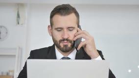 Uomo d'affari Talking sul telefono con il cliente video d archivio
