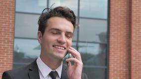 Uomo d'affari Talking sul telefono fuori dell'ufficio archivi video