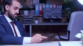 Uomo d'affari a tarda notte nello scorrimento dell'ufficio sul telefono archivi video