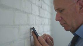 Uomo d'affari triste in testo dell'ufficio facendo uso della rete wireless del telefono cellulare fotografia stock