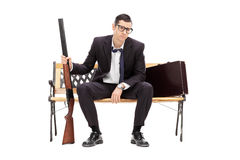 Uomo d'affari turbato che giudica un fucile messo su un banco Fotografie Stock