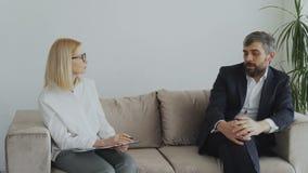 Uomo d'affari turbato che parla dei suoi problemi con lo psicologo femminile archivi video