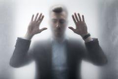 Uomo d'affari turbato con gli occhi chiusi che toccano vetro con le mani dietro la finestra Fotografia Stock