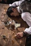 Uomo d'affari ubriaco che dorme alla tavola dopo il partito immagine stock