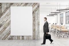 Uomo d'affari in ufficio con il manifesto Immagini Stock Libere da Diritti