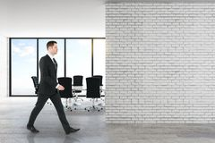 Uomo d'affari in ufficio con il muro di mattoni immagine stock
