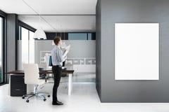 Uomo d'affari in ufficio moderno con il manifesto immagini stock