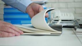 Uomo d'affari in ufficio passare in rassegna le pagine di ordine del giorno che cercano le note finanziarie importanti video d archivio