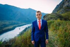 Uomo d'affari in un vestito con il legame rosso sulla cima del mondo con fondo delle montagne fotografia stock