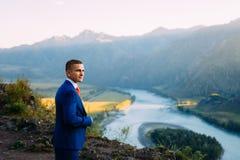Uomo d'affari in un vestito con il legame rosso sulla cima del mondo con fondo delle montagne e del fiume fotografie stock